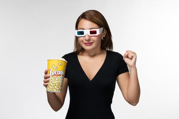 Dサングラスでポップコーンパッケージを保持し、白い表面に笑みを浮かべて正面図若い女性