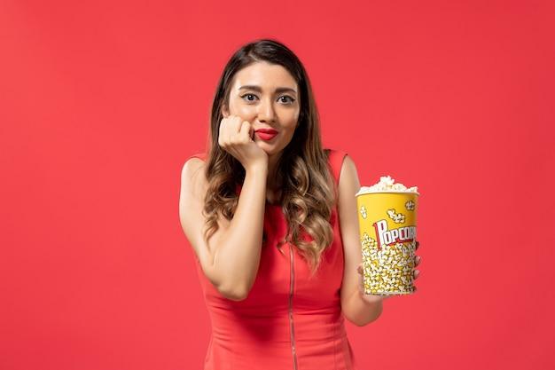 Vista frontale giovane femmina che tiene pacchetto di popcorn sulla superficie rosso chiaro
