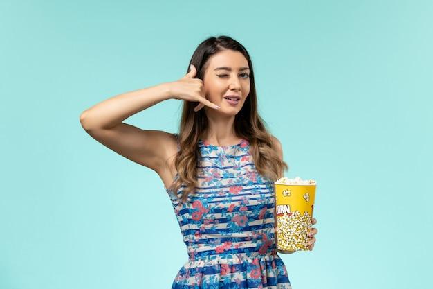 Vista frontale giovane femmina che tiene pacchetto di popcorn e posa sulla superficie blu