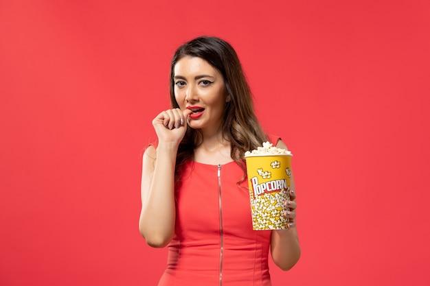 Vista frontale giovane femmina che tiene pacchetto di popcorn sullo scrittorio rosso