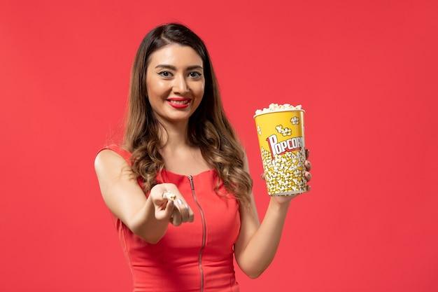 Vista frontale giovane femmina che tiene pacchetto di popcorn e sorridente sulla superficie rossa