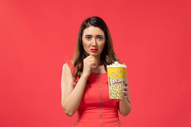 Vista frontale la giovane femmina che tiene il pacchetto del popcorn ha sottolineato sulla superficie rossa