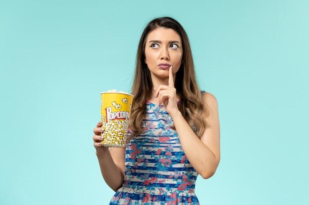 Vista frontale giovane femmina che tiene pacchetto di popcorn e pensando sulla superficie blu