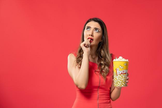 Vista frontale giovane femmina che tiene pacchetto di popcorn pensando sulla superficie rossa