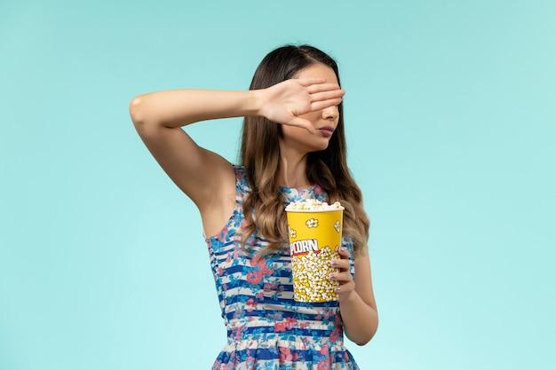 Vista frontale giovane femmina che tiene pacchetto di popcorn e guardare film sulla scrivania blu