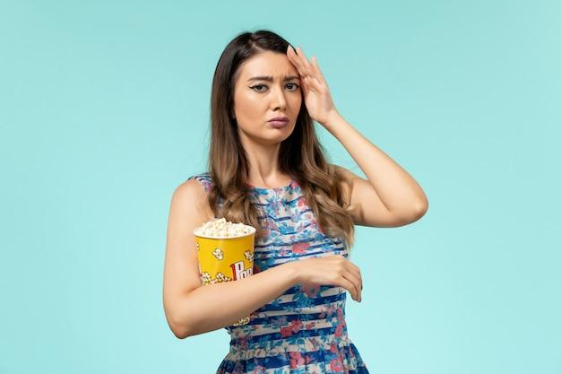 Vista frontale giovane femmina che tiene pacchetto di popcorn guardando film sulla superficie blu