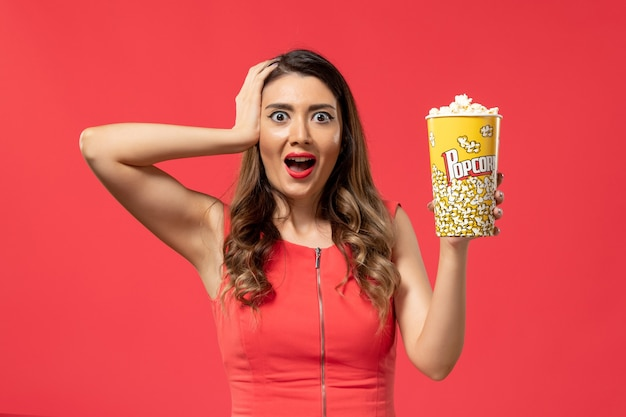 Pacchetto di popcorn della holding della giovane femmina di vista frontale con l'espressione eccitata sullo scrittorio rosso