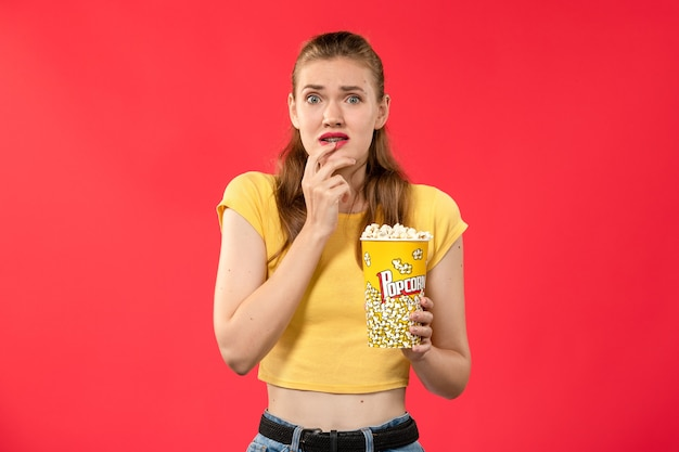 Pacchetto di popcorn della tenuta della giovane femmina di vista frontale con l'espressione spaventata sul film del cinema di film del cinema della parete rosso-chiaro