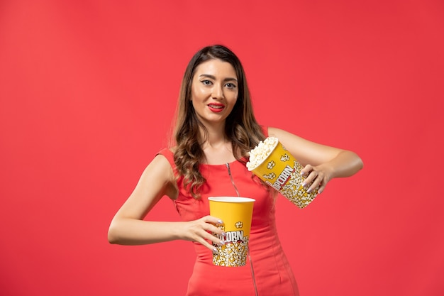 Vista frontale giovane femmina che tiene i pacchetti di popcorn sulla superficie rosso chiaro