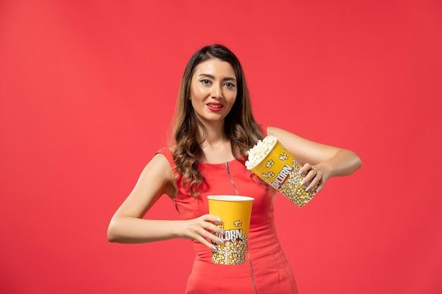 明るい赤の表面にポップコーンパッケージを保持している若い女性の正面図