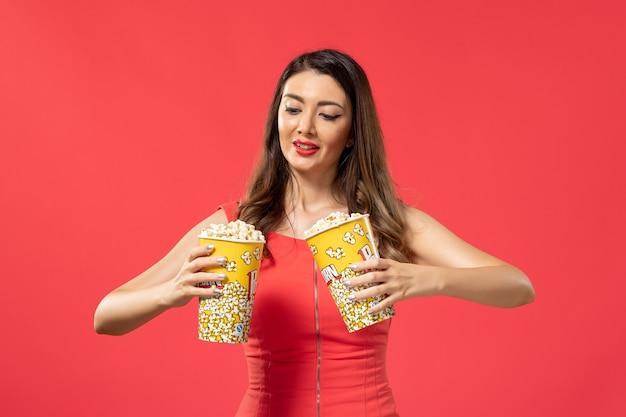 Vista frontale giovane femmina che tiene pacchetti di popcorn sulla superficie rossa