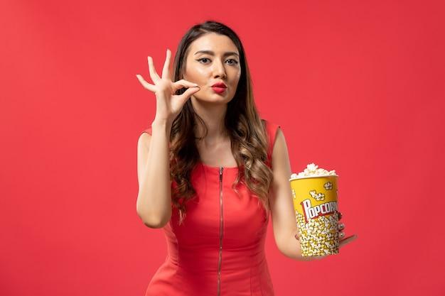 Popcorn femminile giovane della tenuta di vista frontale sullo scrittorio rosso