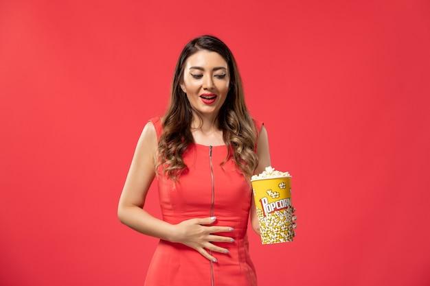 Vista frontale giovane femmina che tiene popcorn sulla superficie rossa