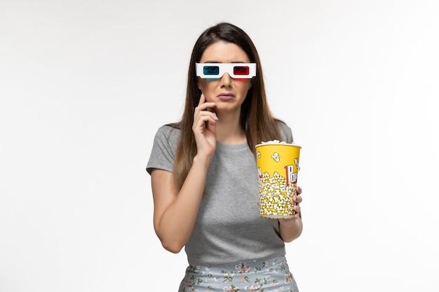Vista frontale giovane femmina che tiene popcorn e guardare film in occhiali da sole d sulla superficie bianca chiara