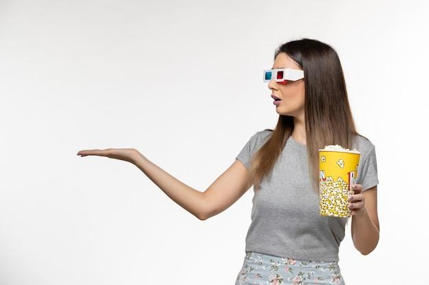 Vista frontale giovane femmina che tiene popcorn e guardare film in occhiali da sole d su superficie bianca