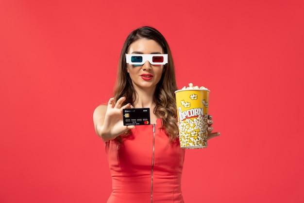 Вид спереди молодая женщина держит попкорн с банковской картой на красной поверхности