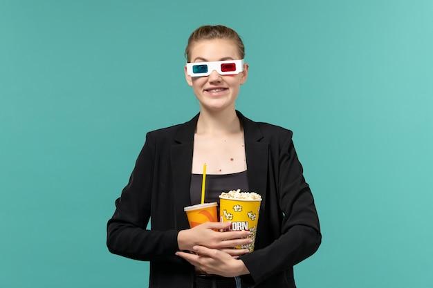 Dサングラスで飲み物とポップコーンを保持し、青い表面で映画を見ている若い女性の正面図