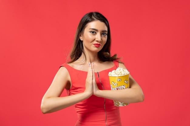 Popcorn della holding della giovane femmina di vista frontale con il sorriso sulla superficie rossa
