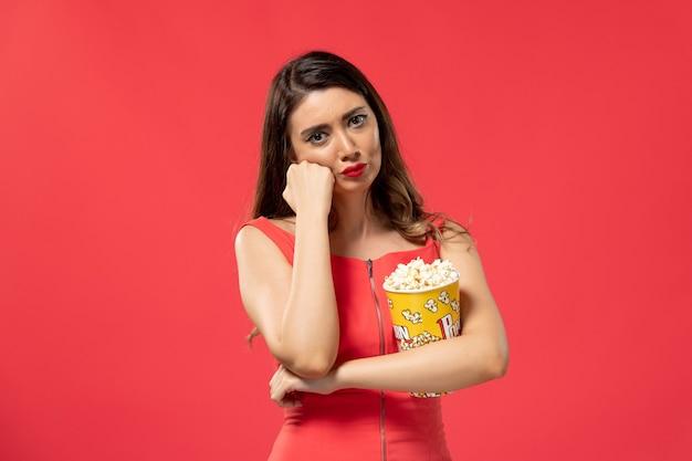 Vista frontale giovane femmina che tiene popcorn con espressione stressata sulla superficie rossa