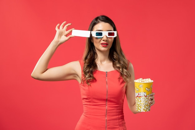 Front view young female holding popcorn with ticket in d sunglasses on red desk
