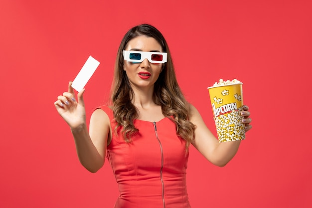 Front view young female holding popcorn with ticket in d sunglasses on red surface