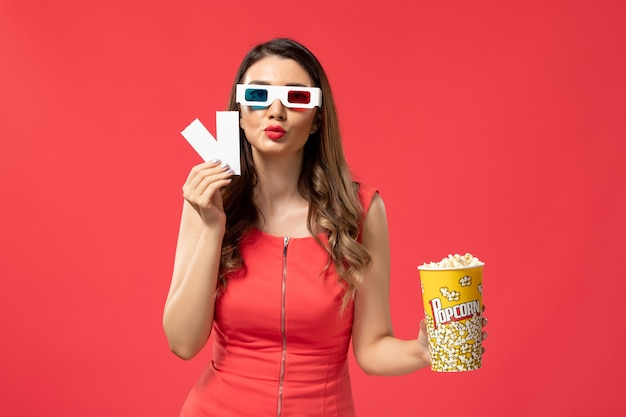 Front view young female holding popcorn with tickets in d sunglasses on light red surface