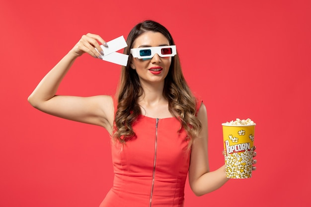Front view young female holding popcorn with tickets in d sunglasses on red desk