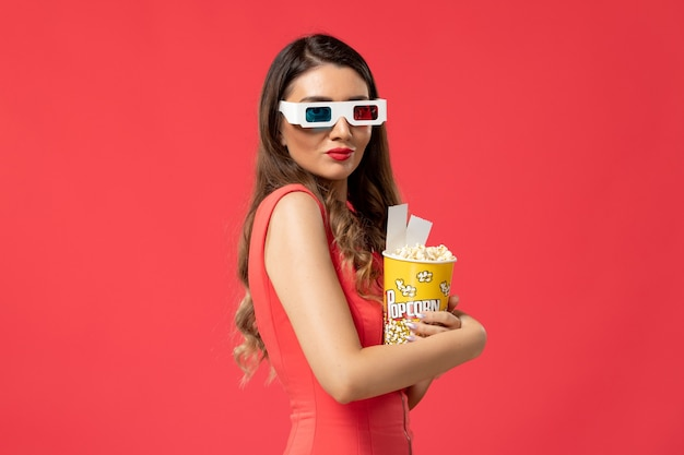 Front view young female holding popcorn with tickets in d sunglasses on red surface