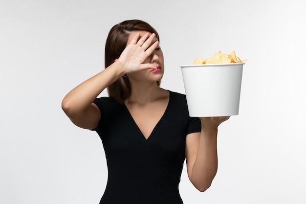 ポテトチップスを保持し、白い表面で面白い映画を見ている若い女性の正面図
