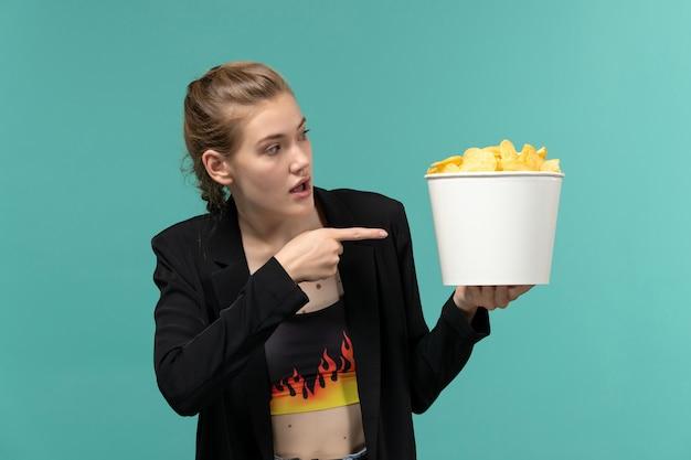 ポテトチップスを保持し、青い表面で映画を見ている若い女性の正面図