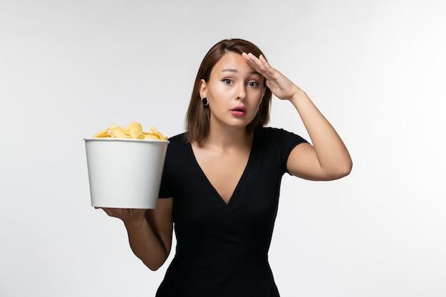 ポテトチップスを保持し、明るい白い表面で映画を見ている若い女性の正面図