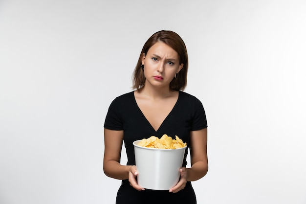 Front view young female holding potato chips and watching movie on white desk