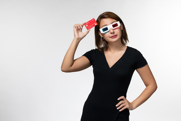 Front view young female holding red bank card in d sunglasses on light-white surface