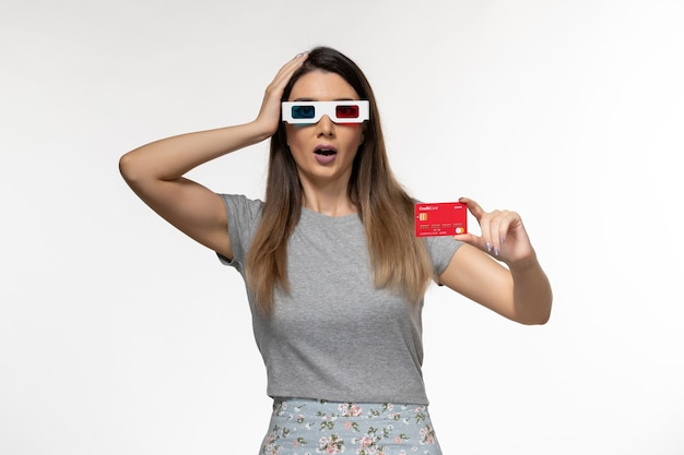 Front view young female holding red bank card in d sunglasses on the light white surface
