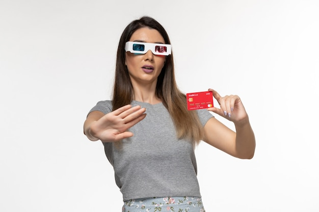 Front view young female holding red bank card in d sunglasses and nervous expression on the light white surface