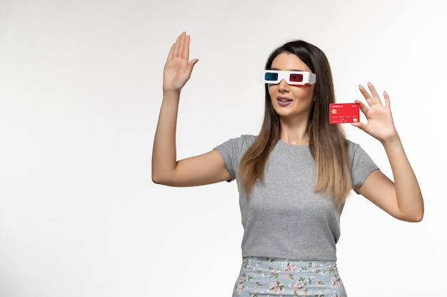 Front view young female holding red bank card in d sunglasses waving her hand on white surface