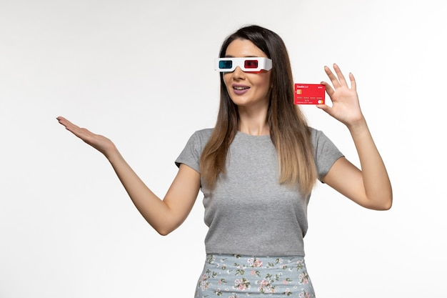 Front view young female holding red bank card in d sunglasses on white desk