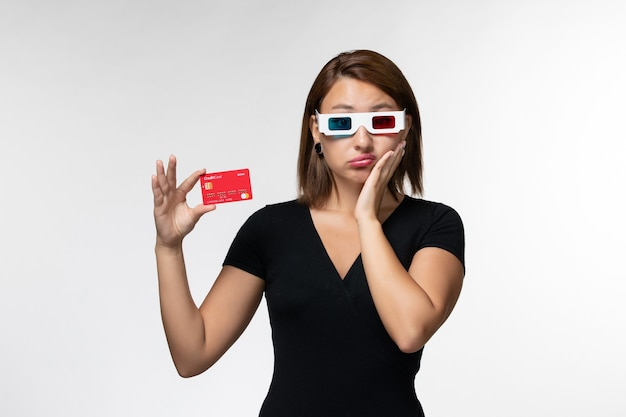 Front view young female holding red bank card in d sunglasses on a white surface