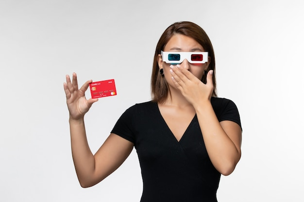 Front view young female holding red bank card in d sunglasses on white surface