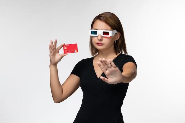 白い表面にdサングラスで赤い銀行カードを保持している正面図若い女性