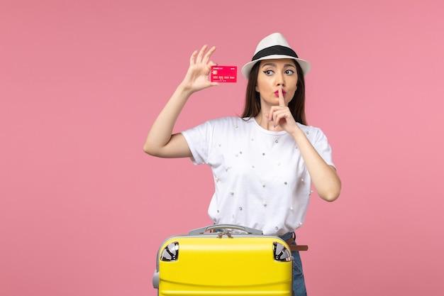 Вид спереди молодая женщина, держащая красную банковскую карту на розовой стене, цвет летнего путешествия