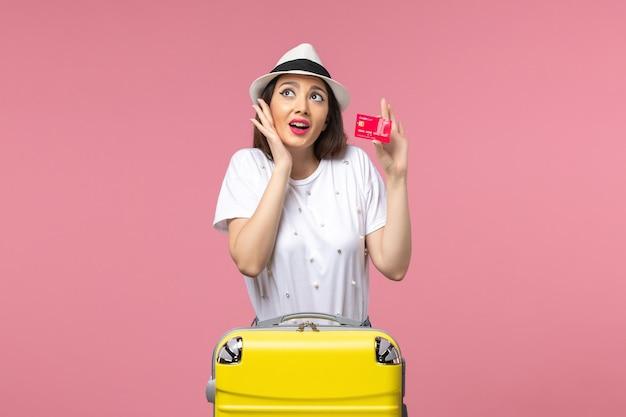 Вид спереди молодая женщина, держащая красную банковскую карту на розовой стене, цветное путешествие летом