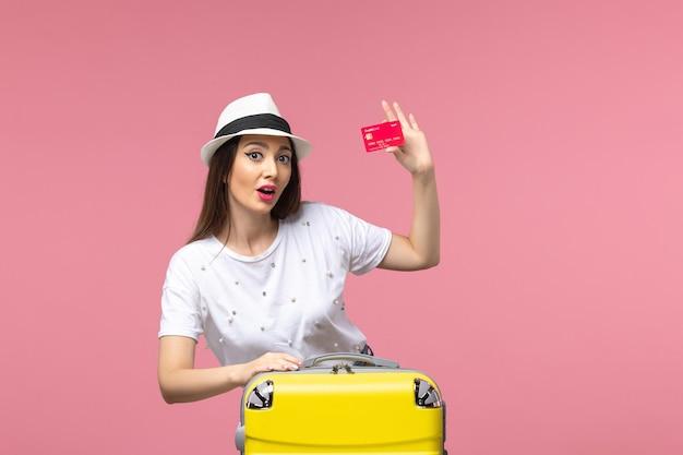 Вид спереди молодая женщина, держащая красную банковскую карту на светло-розовой стене, поездка, летнее путешествие