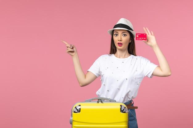 Вид спереди молодая женщина, держащая красную банковскую карту на светло-розовой стене, цвет летнего путешествия