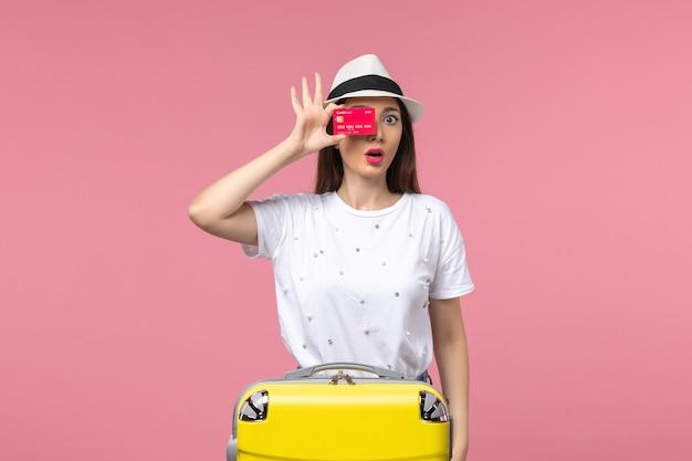 Вид спереди молодая женщина, держащая красную банковскую карту на светло-розовой стене, летнее путешествие