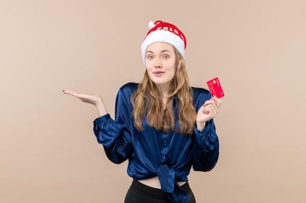 분홍색 배경 크리스마스 돈 사진 휴가 새 해 감정에 빨간 은행 카드를 들고 전면보기 젊은 여성
