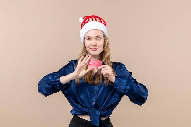 Вид спереди молодая женщина держит красную банковскую карту на розовом столе праздник рождественские деньги фото новогодние эмоции