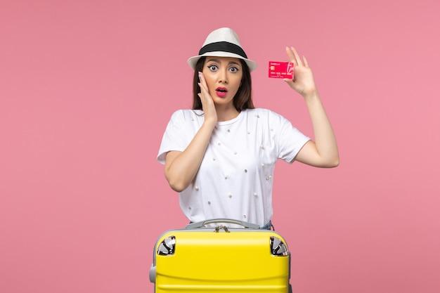 Вид спереди молодая женщина, держащая красную банковскую карту на розовой стене, цветная поездка, летнее путешествие