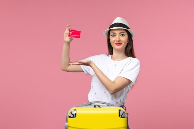 Вид спереди молодая женщина держит красную банковскую карту на розовой стене летнее путешествие