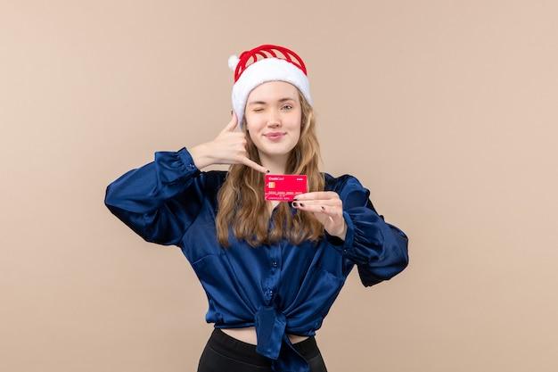 Вид спереди молодая женщина держит красную банковскую карту на розовом фоне праздничное фото новый год рождество деньги эмоции